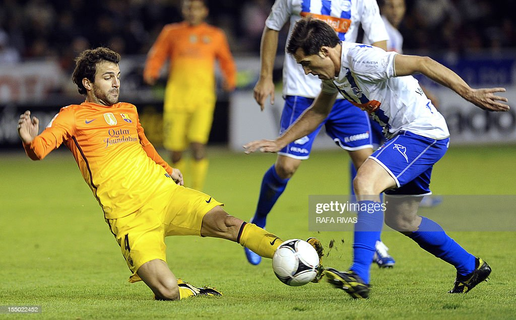 Barcelona's midfielder Cesc Fabregas (L) tackles Alaves' defender Sendoa Aguirre (R) during the Copa del Rey (King's Cup) first-leg football match between CD Alaves and FC Barcelona at the Mendizorroza stadium in Vitoria on October 30, 2012. AFP PHOTO / RAFA RIVAS