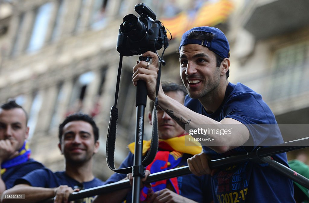Barcelona's midfielder Cesc Fabregas takes a picture as he and his teammates parade on a bus through a crowd of supporters celebrating in the streets of Barcelona on May 13, 2013, two days after their team won the Spanish league. The Catalans didn't even need to set foot on the pitch to seal the title on May 11 as Real Madrid's 1-1 draw with Espanyol meant Barca had already been crowned champions before their 2-1 win over Atletico Madrid on May 12, 2013. AFP PHOTO/ LLUIS GENE