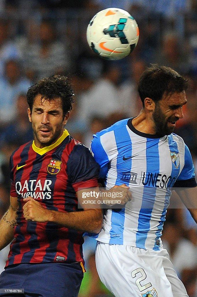 Barcelona's midfielder Cesc Fabregas (L) vies for the ball with Malaga's defender Jesus Gamez during the Spanish league football match Malaga CF vs FC Barcelona at Rosaleda stadium in Malaga on August 25, 2013. Barcelona won 1-0.