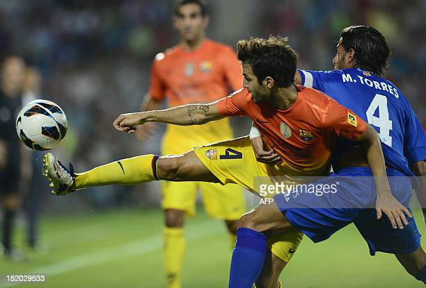 Barcelona's midfielder Cesc Fabregas vies with Getafe's defender Miguel Torres during the Spanish league football match Getafe vs Barcelona at...