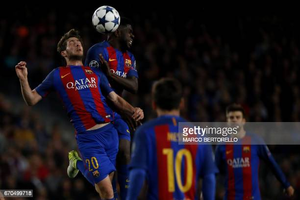 Barcelona's midfielder Sergi Roberto from Spain jumps for the ball with Barcelona's defender Samuel Umtiti from France during the UEFA Champions...