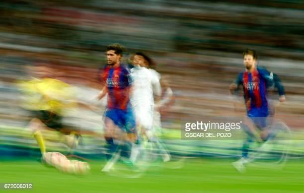 TOPSHOT Barcelona's midfielder Sergi Roberto Real Madrid's Brazilian defender Marcelo and Barcelona's defender Gerard Pique run behind the ball...