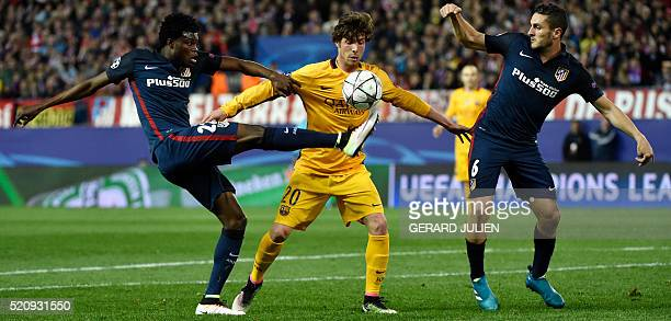 Barcelona's midfielder Sergi Roberto vies with Atletico Madrid's Ghanaian midfielder Thomas Partey and Atletico Madrid's midfielder Koke during the...