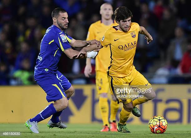 Barcelona's midfielder Sergi Roberto vies with Getafe's Algerian midfielder Medhi Lacen during the Spanish league football match Getafe CF vs FC...