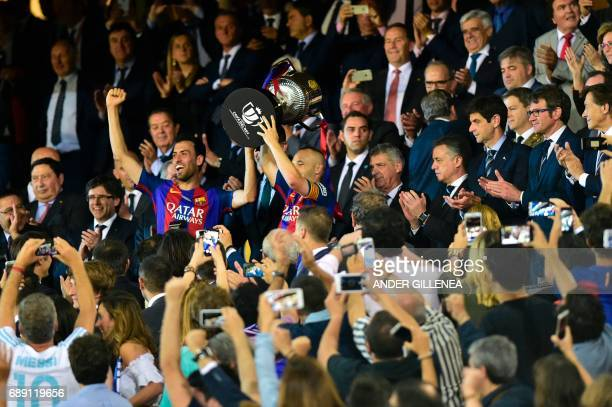 Barcelona's midfielder Sergio Busquets and Barcelona's midfielder Andres Iniesta hold up the trophy after the team won the Spanish Copa del Rey final...