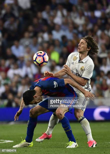 Barcelona's midfielder Sergio Busquets vies with Real Madrid's Croatian midfielder Luka Modric during the Spanish league football match Real Madrid...