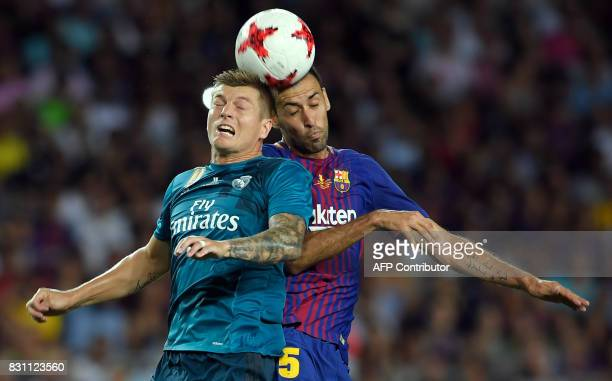 Barcelona's midfielder Sergio Busquets vies with Real Madrid's German midfielder Toni Kroos during the Spanish Supercup first leg football match FC...
