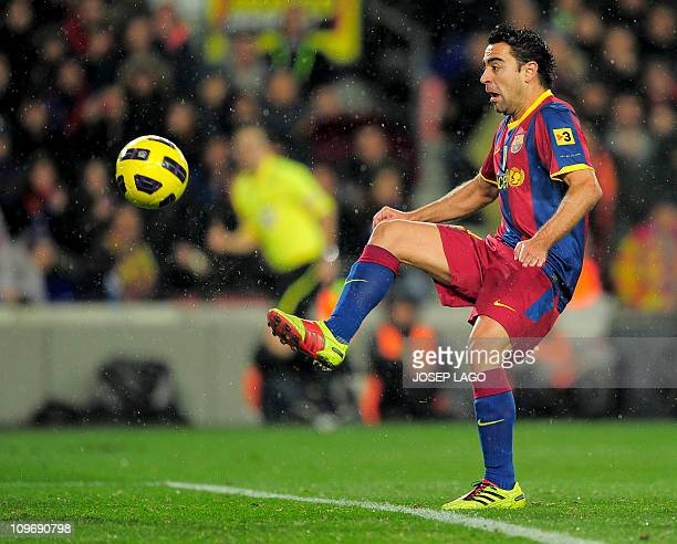 Barcelona's midfielder Xavi Hernandez scores his team's first goal to Real Madrid during the Spanish league 'clasico' football match FC Barcelona vs...