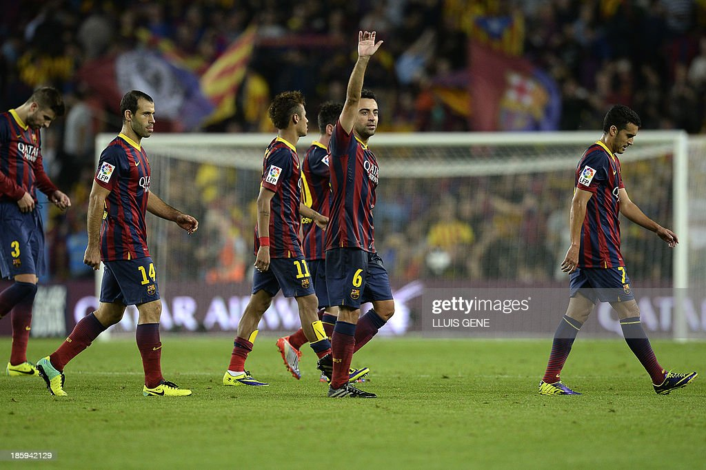 Barcelona's midfielder Xavi Hernandez (C) waves (2ndR) at the end of the Spanish league Clasico football match FC Barcelona vs Real Madrid CF at the Camp Nou stadium in Barcelona on October 26, 2013. Barcelona won 2-1.
