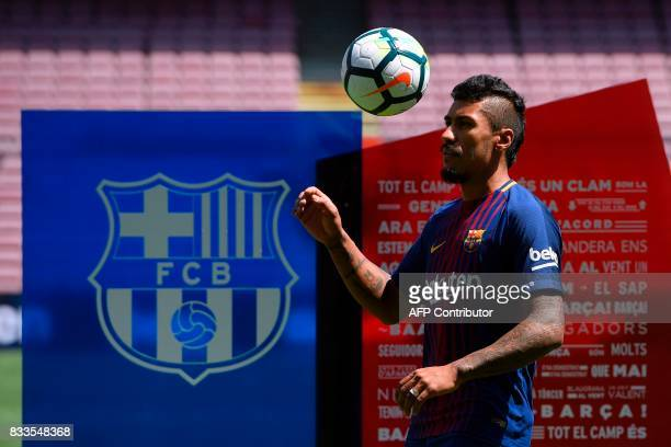 Barcelona's new Brazilian football player Paulinho Bezerra eyes a ball during his official presentation after signing his new contract with the...