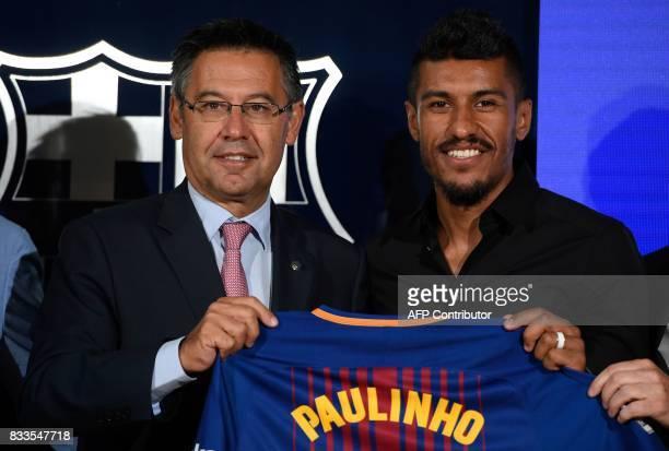 Barcelona's new Brazilian football player Paulinho Bezerra poses with his new jersey and Barcelona's president Josep Maria Bartomeu during his...