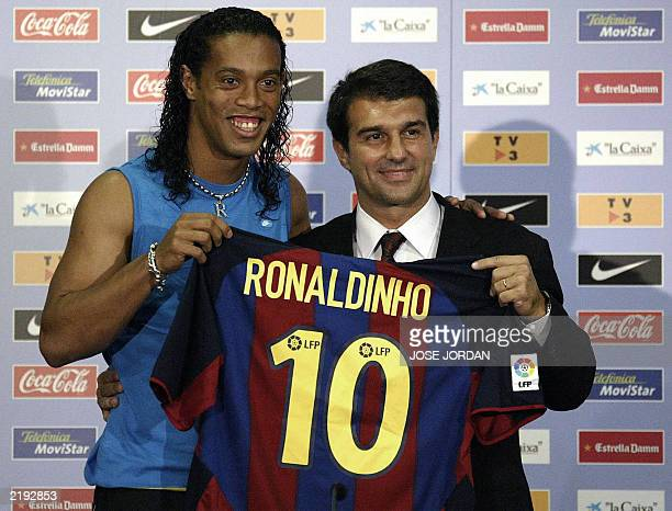 Barcelona's new Brazilian soccer star Ronaldinho and Barcelona newlyelected president Joan Laporta hold Ronaldinho 's jersey during his official...