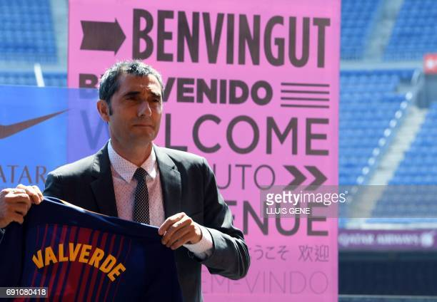 Barcelona's new coach Ernesto Valverde holds a jersey with his name on it during his official presentation at the Camp Nou stadium in Barcelona on...