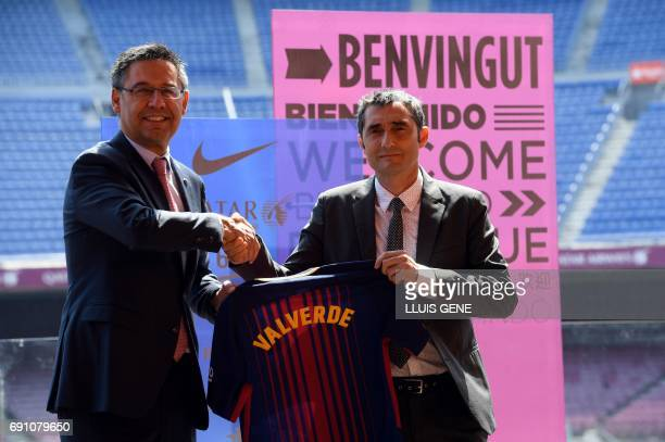 Barcelona's new coach Ernesto Valverde shakes hands with Barcelona's president Josep Maria Bartomeu as they hold a jersey with Valverde's name on it...