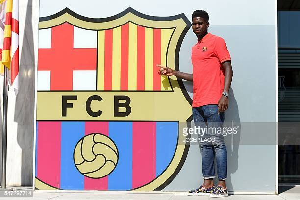 Barcelona's new player French defender Samuel Umtiti gestures as he poses outside the Camp Nou stadium in Barcelona prior to signing his new contract...