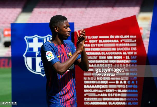 Barcelona's new player Ousmane Dembele applauds as he poses at the Camp Nou stadium in Barcelona during his official presentation by the Catalan...