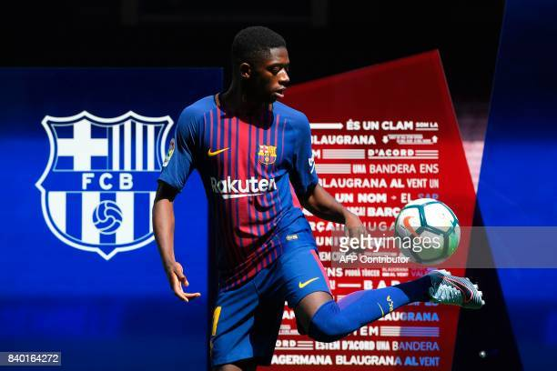 Barcelona's new player Ousmane Dembele controls a ball at the Camp Nou stadium in Barcelona during his official presentation by the Catalan football...