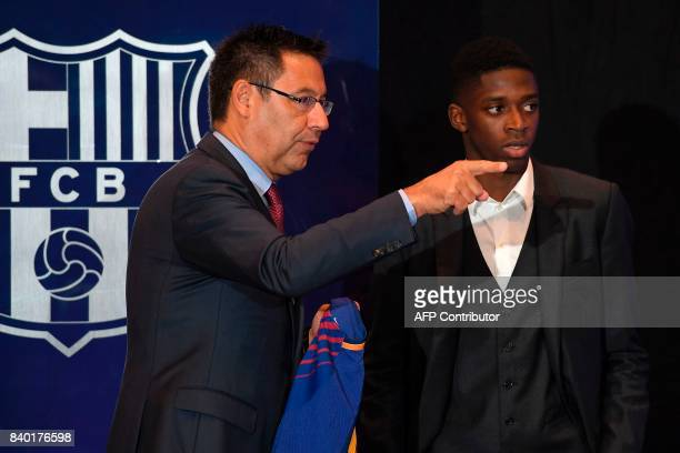 Barcelona's new player Ousmane Dembele looks on next to Barcelona's president Josep Maria Bartomeu at the Camp Nou stadium in Barcelona during his...