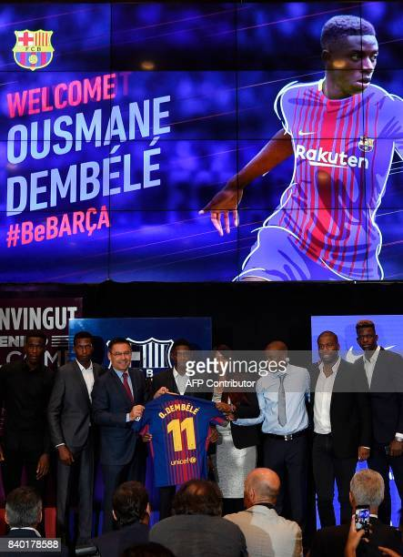 Barcelona's new player Ousmane Dembele poses with his new jersey next to Barcelona's president Josep Maria Bartomeu and Dembele's relatives at the...