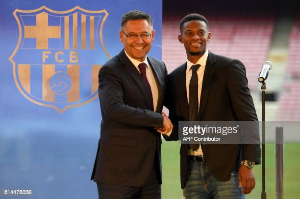 Barcelona's new player Portuguesse Nelson Semedo shakes hands with Barcelona's president Josep Maria Bartomeu as they pose during his official...