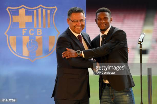 Barcelona's new Portuguese player Nelson Semedo poses with his new jersey as he shakes hands with Barcelona's president Josep Maria Bartomeu during...