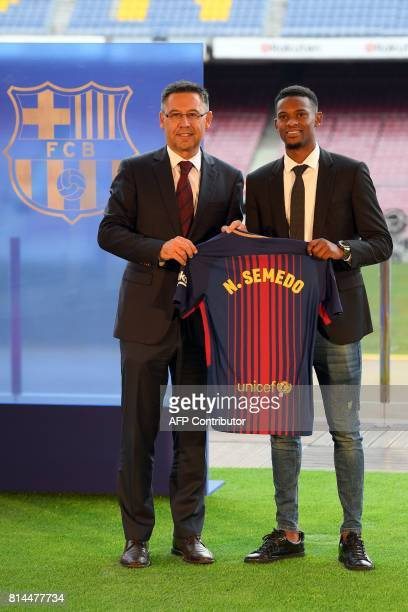 Barcelona's new Portuguese player Nelson Semedo poses with his new jersey past Barcelona's president Josep Maria Bartomeu during his official...