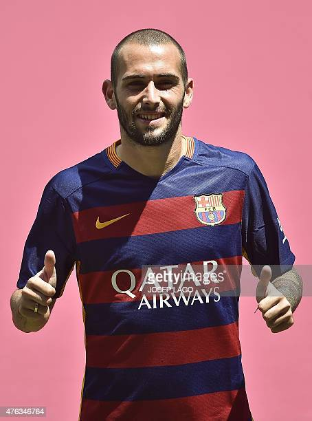 Barcelona's new Spanish defender Aleix Vidal gives the thumbs up as he poses with his new jersey during his official presentation at the Camp Nou...