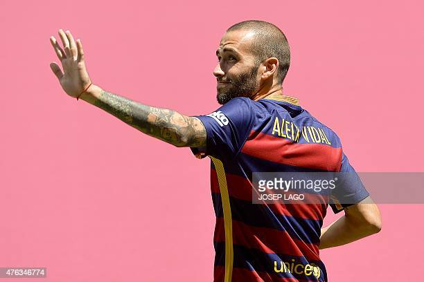 Barcelona's new Spanish defender Aleix Vidal waves to supporters during his official presentation at the Camp Nou stadium in Barcelona on June 8 2015...