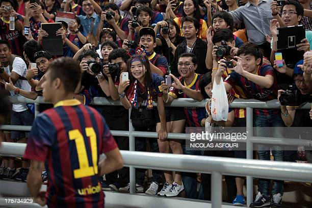 FC Barcelona's Neymar is cheered by his fans as he enter the pitch to play their exhibition match against Thailand's national football team at the...