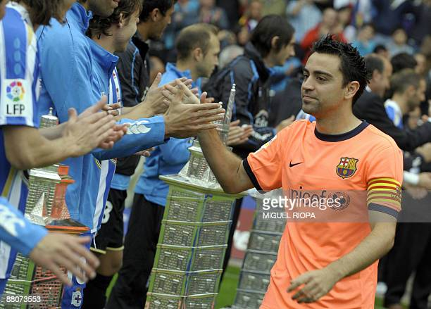 FC Barcelona´s player Xavi Hernandez is congratulated by Deportivo Coruna's players before their Spanish first league football match at the Riazor...