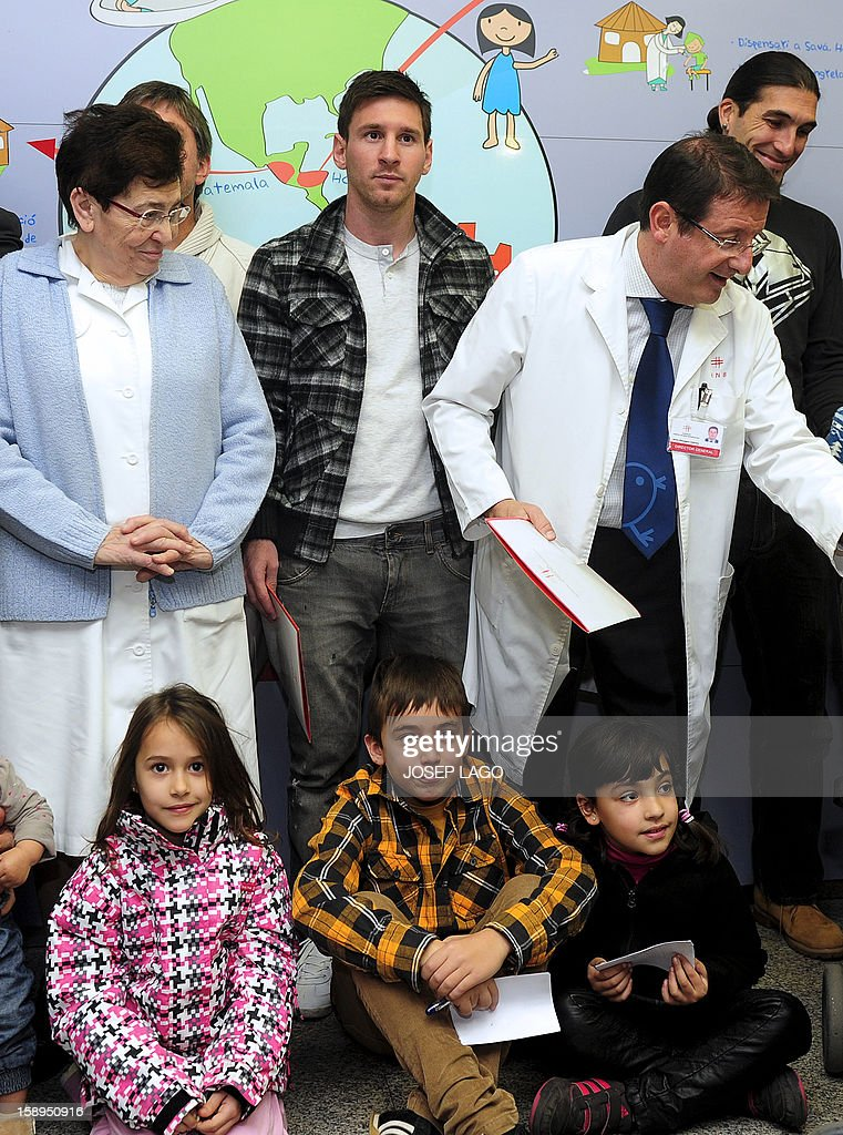 Barcelona's players Argentinian forward Lionel Messi (C) poses with doctors and childen during a visit to the Hospital de Nens (the Children's Hospital) in Barcelona on January 4, 2013. AFP PHOTO / JOSEP LAGO