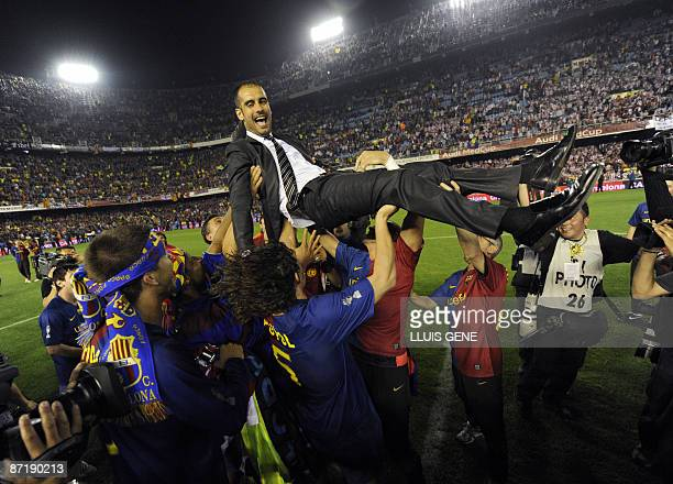 Barcelona´s players lift their coach Pep Guardiola after winning the Spanish King´s Cup final match against on May 13 2009 at the Mestalla stadium in...