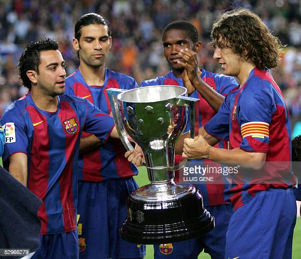 FC Barcelona's players Xavi Mexican Rafael Marquez Samuel Eto'o of Cameroon and Carles Puyol show of the Spanish League title trophy after defeating...