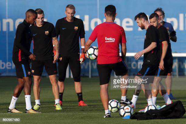Barcelona's Portuguese defender Nelson Semedo and Barcelona's Argentinian forward Lionel Messi play with teammates during a training session at the...