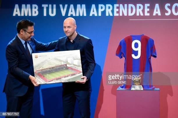 Barcelona's president Josep Maria Bartomeu and son of late Dutch football star Johan Cruyff Jordi Cruyff pose with a photo of the project of new...