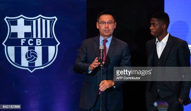 Barcelona's president Josep Maria Bartomeu delivers a speech next to Barcelona's new player Ousmane Dembele at the Camp Nou stadium in Barcelona...