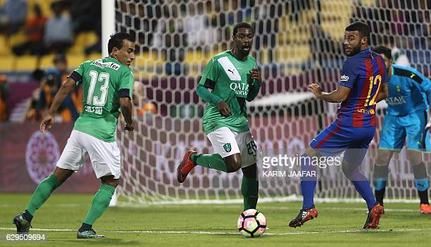 FC Barcelona's Rafinha vies for the ball with AlAhly's Mohamed Abdel Shafy and Mohamed Aman during a friendly football match between FC Barcelona and...