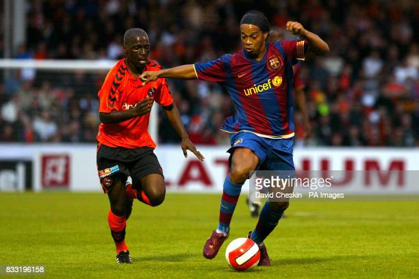 Barcelona's Ronaldinho holds off Dundee United's Morgaro Gomis during the preseason friendly match at Tannadice Park Dundee