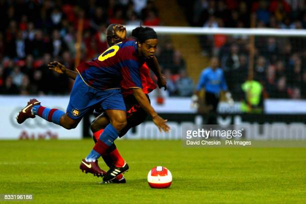Barcelona's Ronaldinho tussles with Dundee United's Morgaro Gomis during the preseason friendly match at Tannadice Park Dundee