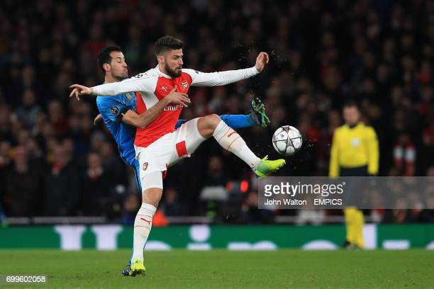 Barcelona's Sergio Busquets and Arsenal's Olivier Giroud battle for the ball