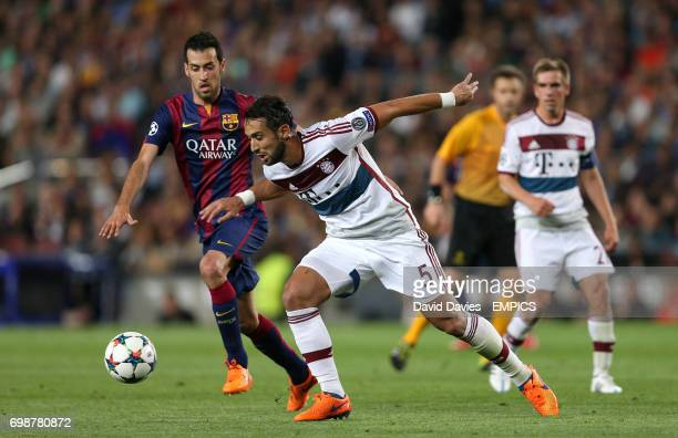 Barcelona's Sergio Busquets and Bayern Munich's Medhi Benatia battle for the ball