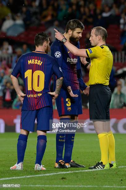 Barcelona's Spanish defender Gerard Pique talks to the referee beside Barcelona's Argentinian forward Lionel Messi during the UEFA Champions League...