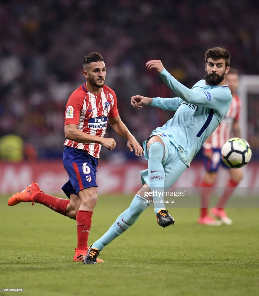Barcelona's Spanish defender Gerard Pique (R) vies with Atletico Madrid's Spanish midfielder Koke during the Spanish league football match Club Atletico de Madrid vs FC Barcelona at the Wanda Metropolitano stadium in Madrid on October 14, 2017. /