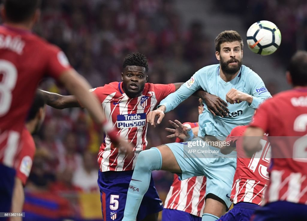 Barcelona's Spanish defender Gerard Pique (R) vies with Atletico Madrid's Ghanaian midfielder Thomas during the Spanish league football match Club Atletico de Madrid vs FC Barcelona at the Wanda Metropolitano stadium in Madrid on October 14, 2017. /