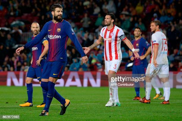 Barcelona's Spanish defender Gerard Pique walks on the field beside Olympiacos' Spanish defender Alberto Botia during the UEFA Champions League group...