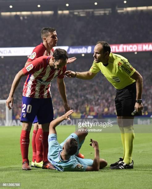 Barcelona's Spanish forward Gerard Deulofeu lies on the field as Atletico Madrid's Spanish defender Juanfran talks to him beside Spanish referee...