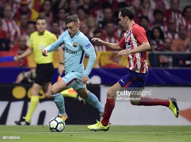 Barcelona's Spanish forward Gerard Deulofeu vies with Atletico Madrid's Uruguayan defender Diego Godin during the Spanish league football match Club...