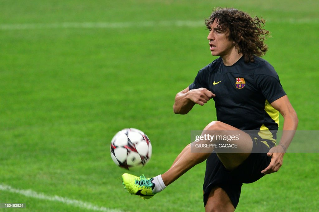 Barcelona's Spanish midfielder and captain Carles Puyol controls the ball during a training session on October 21, 2013 in San Siro Stadium in Milan, on the eve of the UEFA Champions League football match between AC Milan and FC Barcelona.