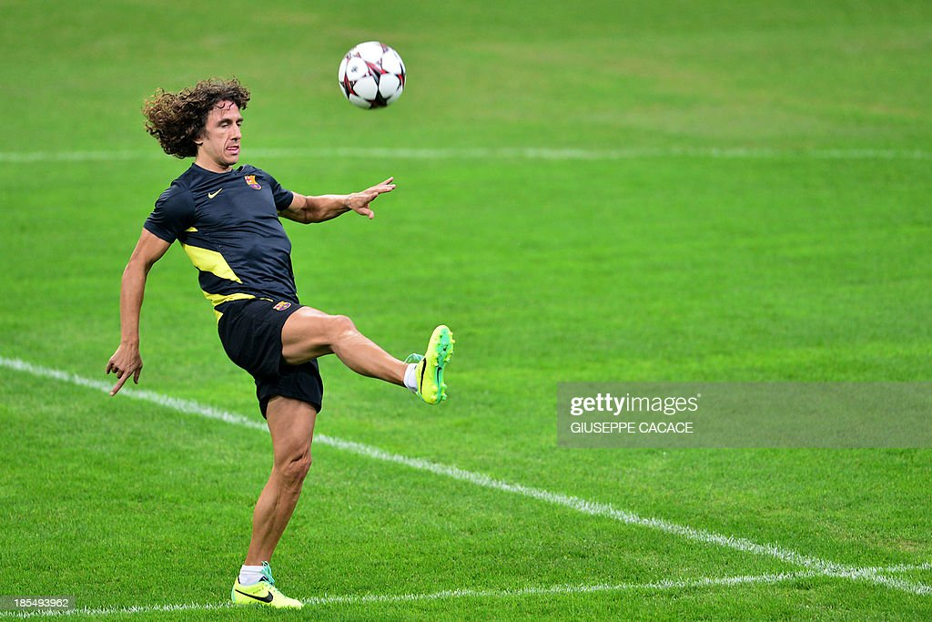Barcelona's Spanish midfielder and captain Carles Puyol juggles with the ball during a training session on October 21, 2013 in San Siro Stadium in Milan, on the eve of the UEFA Champions League football match between AC Milan and FC Barcelona.