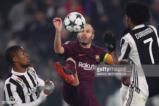Barcelona's Spanish midfielder Andres Iniesta fights for the ball with Juventus' forward from Brazil Douglas Costa and Juventus' forward from...